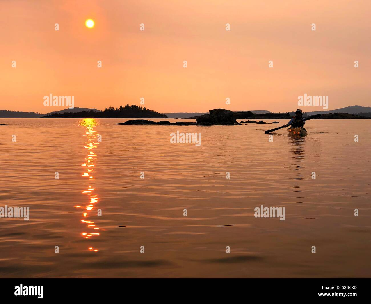 Kayaker paddle into dramatic sunset at Desolation Sound during forest fires in summer - Stock Image