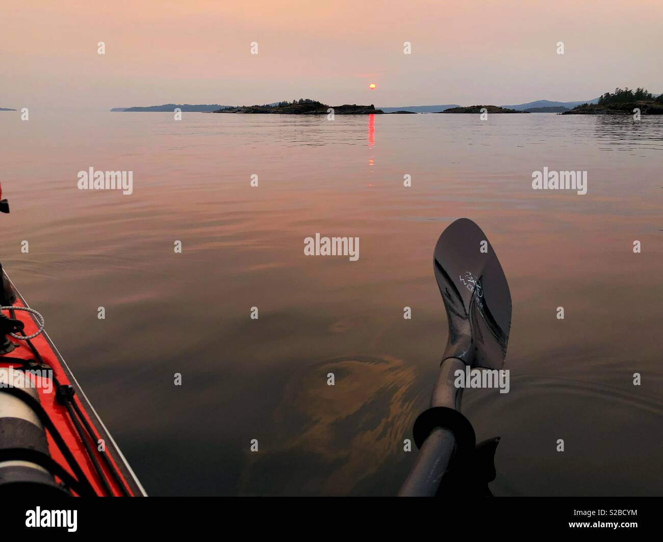 Kayaking at Unsettling sunset at Desolation Sound during summer forest fires in BC - Stock Image
