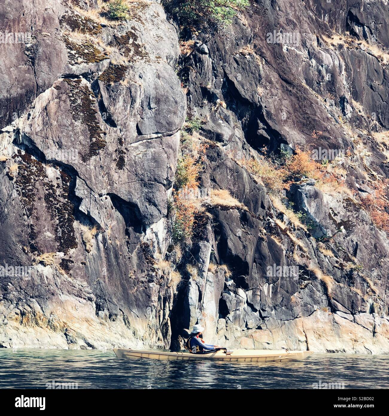 Kayaker near the cliff at Desolation sound, BC, Canada - Stock Image