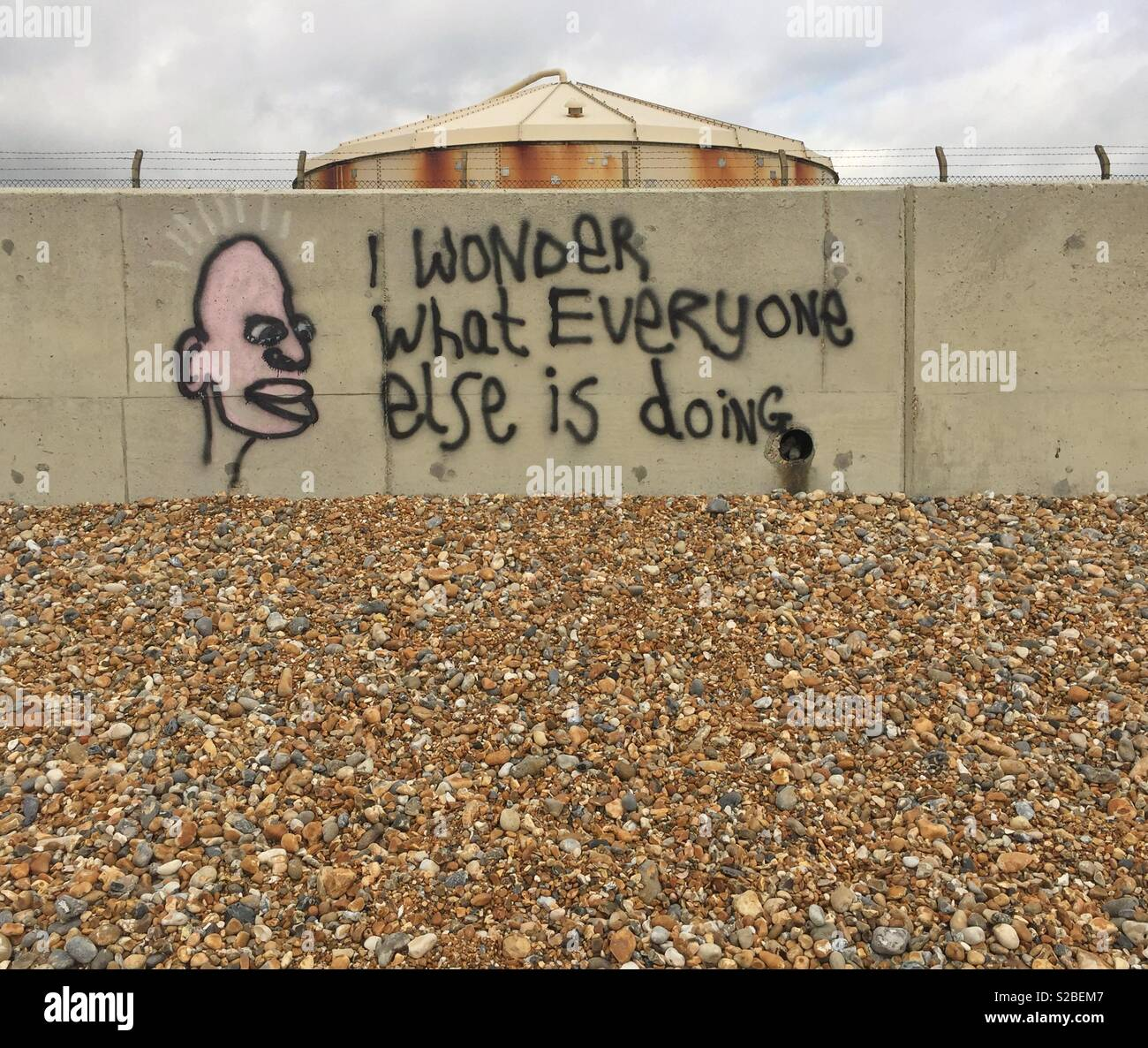Humourous graffiti on a sea wall by a pebbled beach in Southwick near Brighton - Stock Image