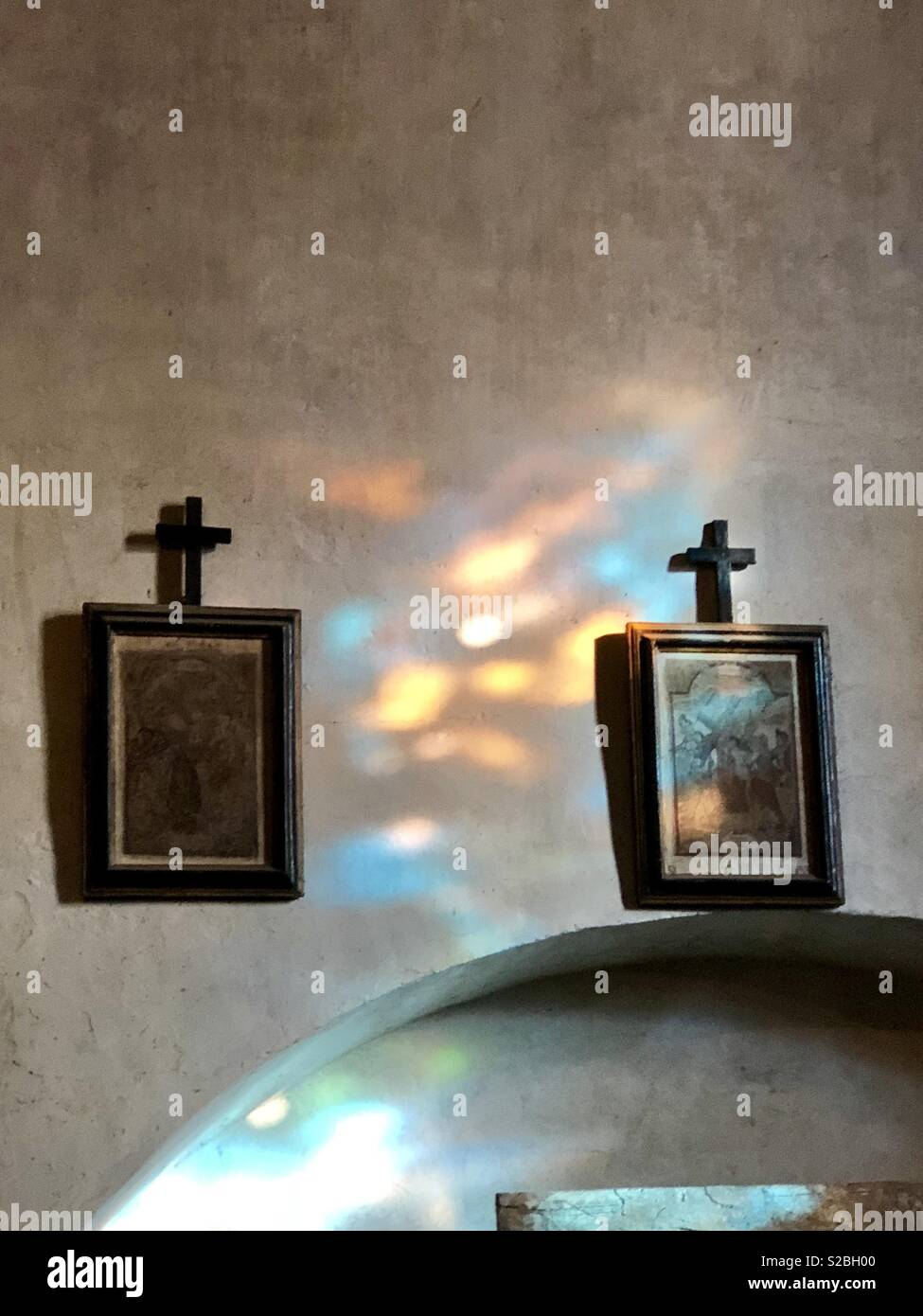 Stain glass window reflections on artwork in San Damiano chapel in Asissi Italy Stock Photo
