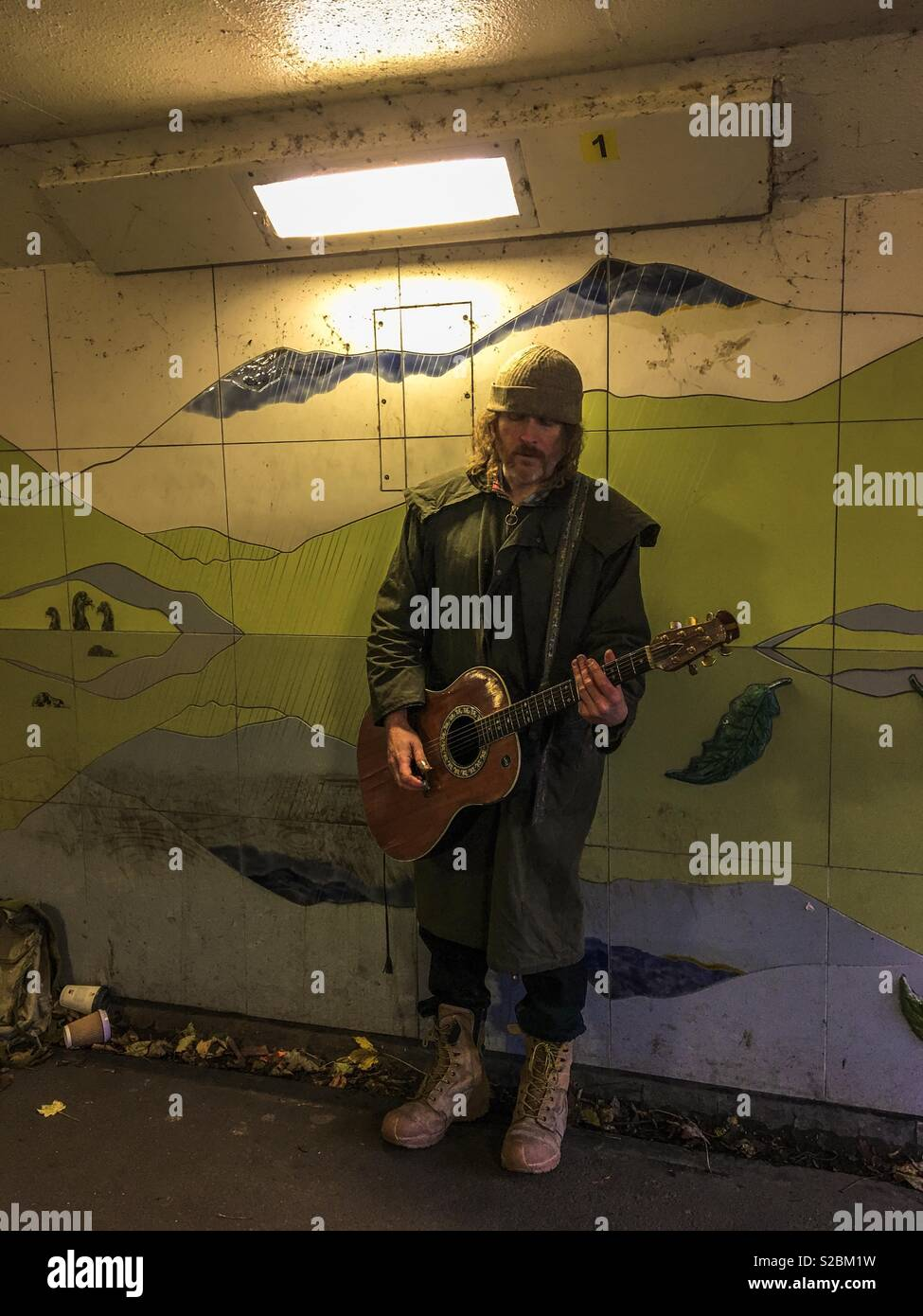 A busker in a woolly hat playing an acoustic guitar in the subway in  Keswick surrounded b2ee96e1c3c6