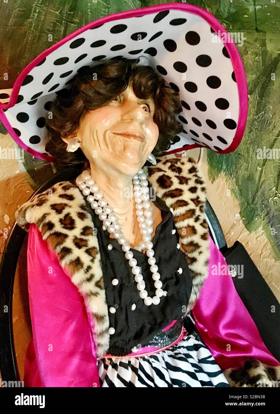 Mannequin of elderly woman sitting in black chair with black purse wearing black white and pink polka dotted hat, pink coat with faux leopard fur trim, pearl strands, black blouse  zebra print skirt - Stock Image