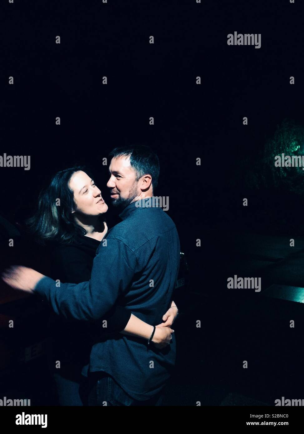Happy couple in an intimate moment hugging and laughing. - Stock Image
