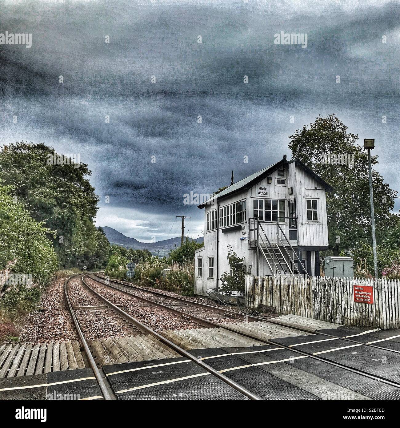 Blair Atholl train station, railway crossing, rail tracks and road, Perthshire, Scotland - Stock Image