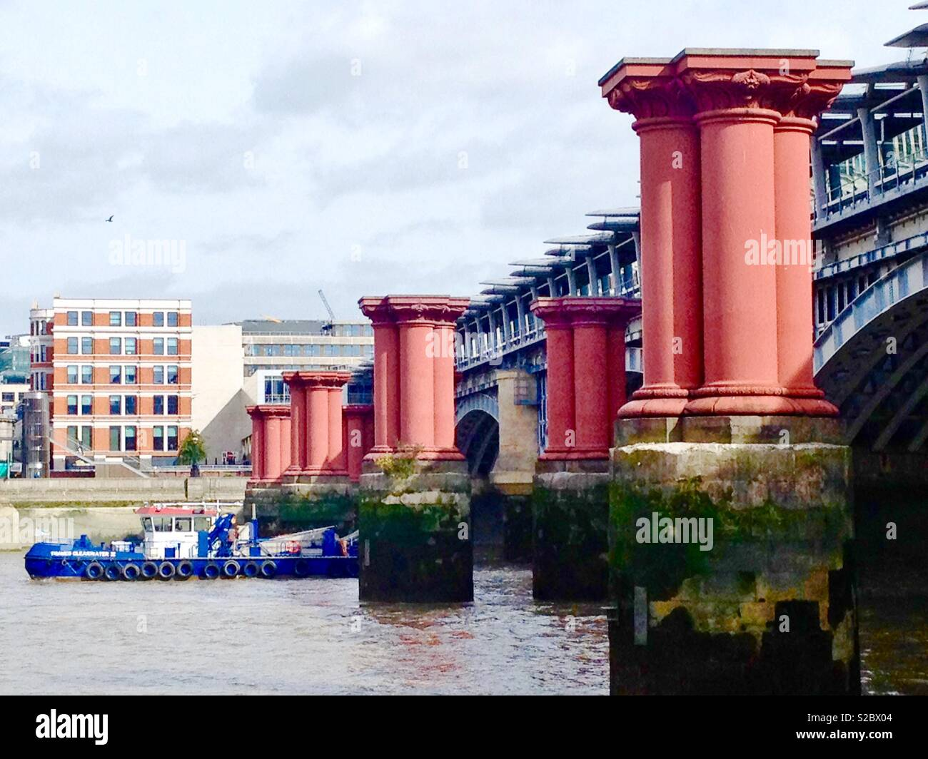 Surviving support columns for the Victorian railway bridge in front of the modern railway station bridge Stock Photo