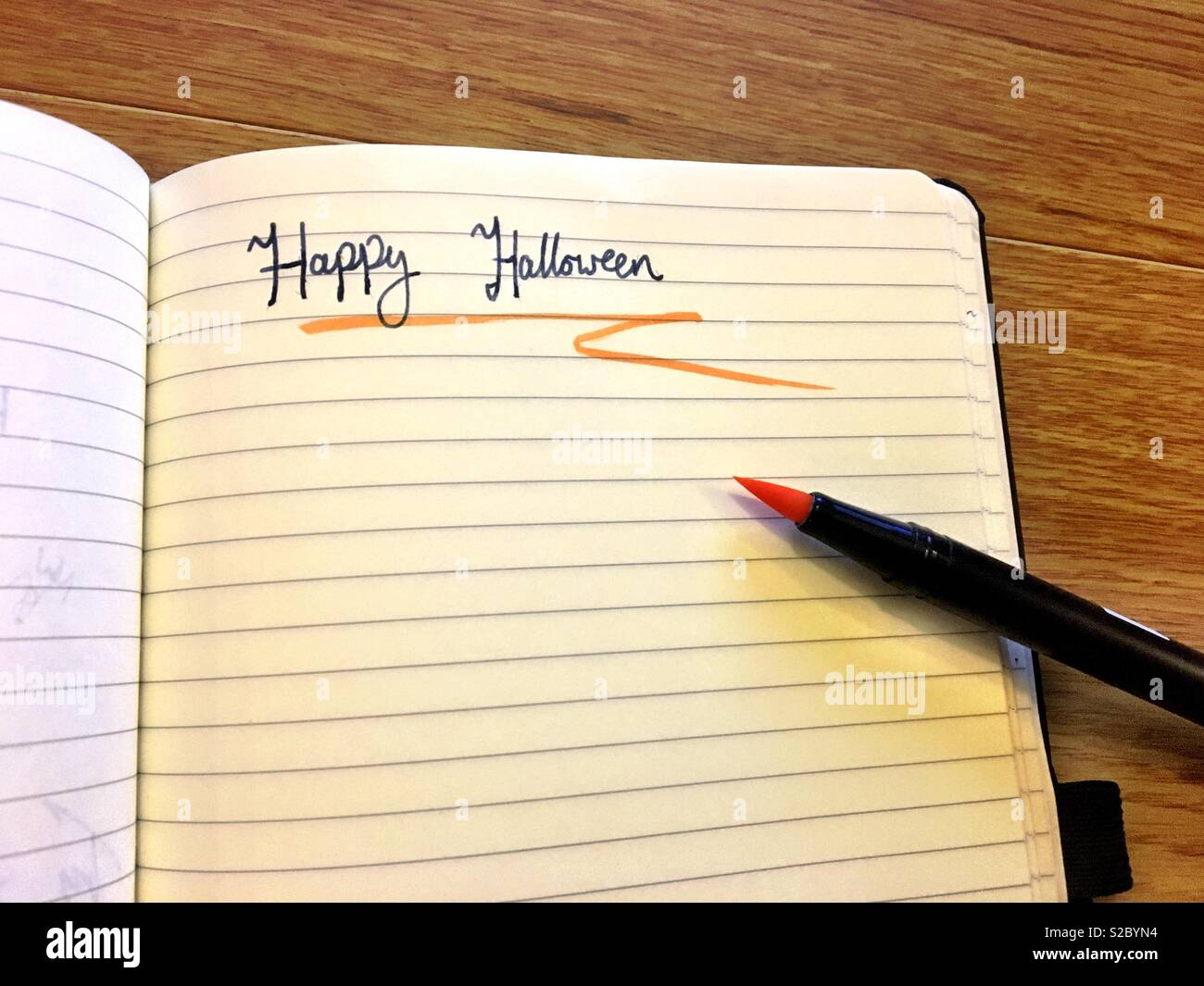 Happy Halloween hand written in a lined notebook with a blue ink fountain pen underlined with an orange feathered brush pen - Stock Image
