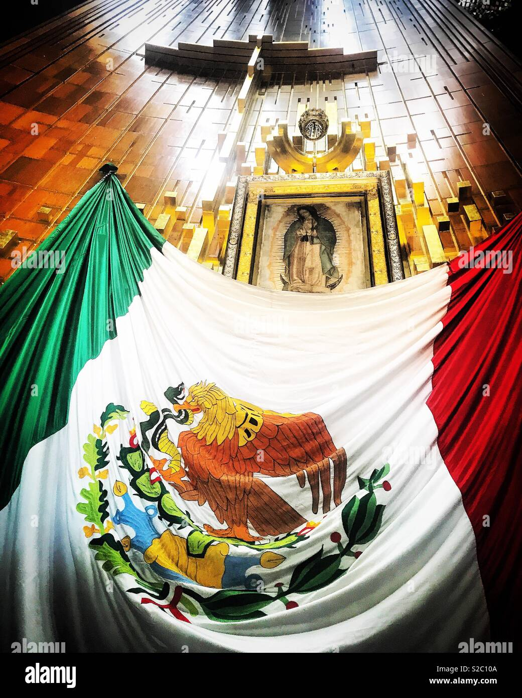 The Mexican flag covers the altar of Our Lady of Guadalupe in Mexico City, Mexico - Stock Image