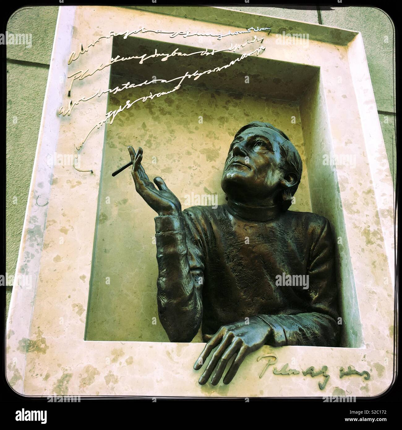 Sculpture of a man smoking out of a window. Budapest, Hungary. - Stock Image
