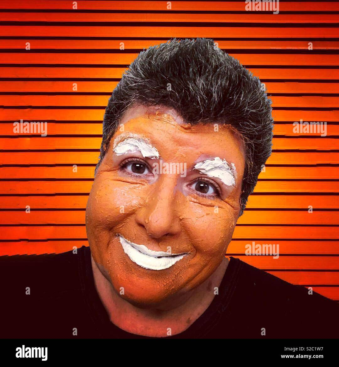 A comical self portrait of a dark haired woman wearing an orange face mask against an orange background - Stock Image
