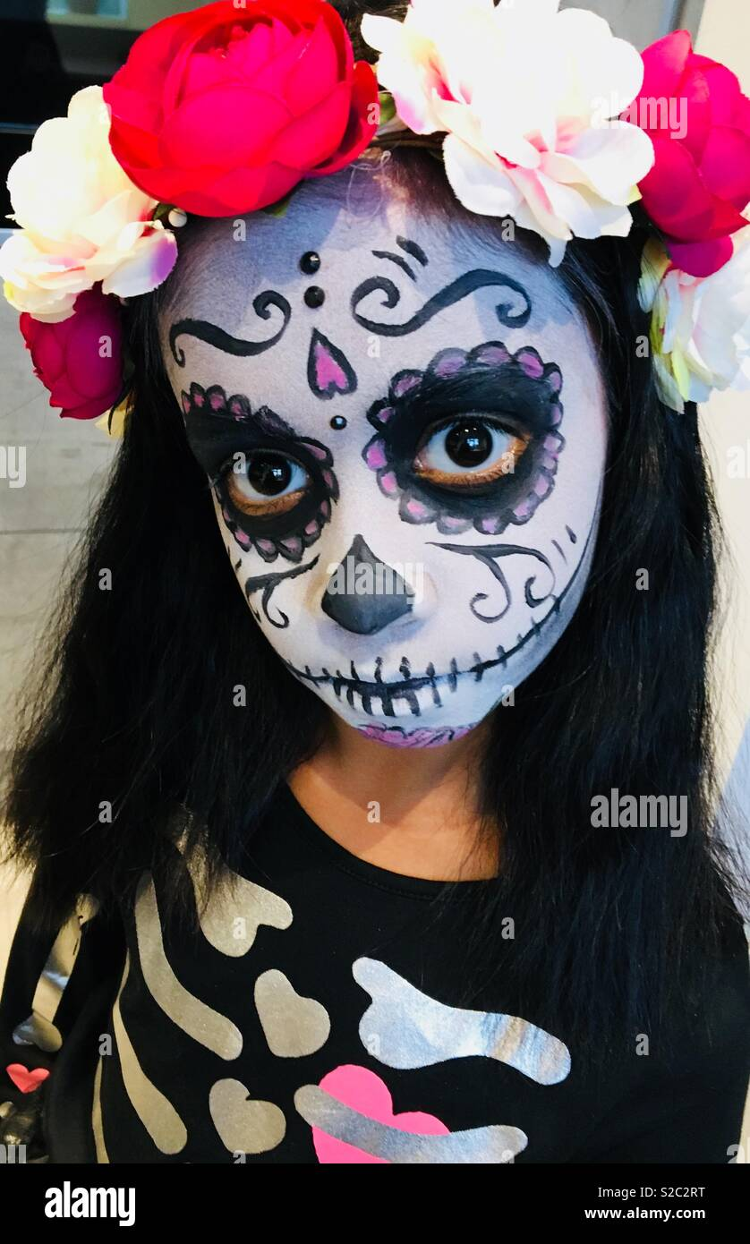Girl dressed up in skeleton day of the dead costume for Halloween - Stock Image