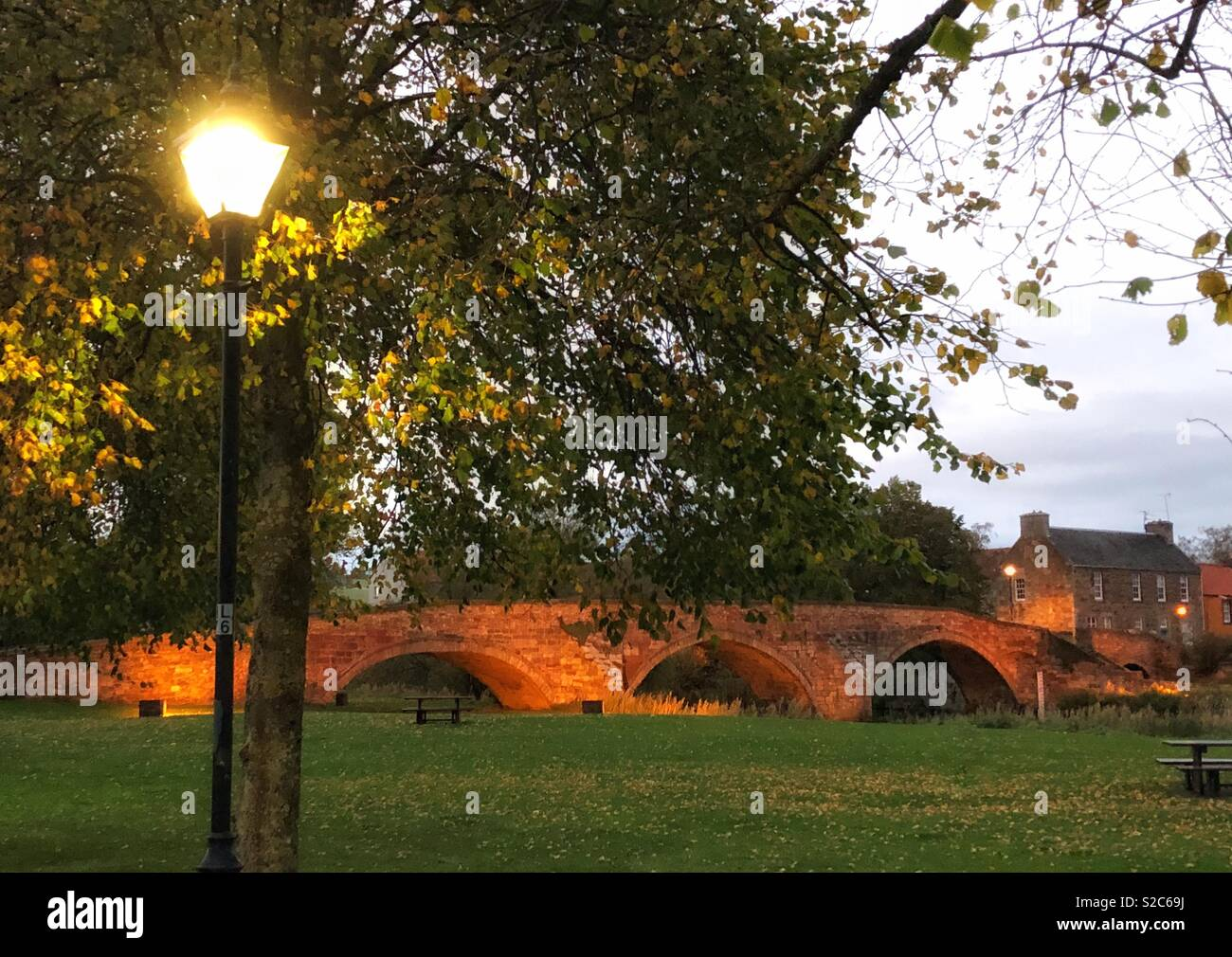 Historic arched Nungate Bridge lit up at twilight, Haddington, East Lothian, Scotland, UK - Stock Image