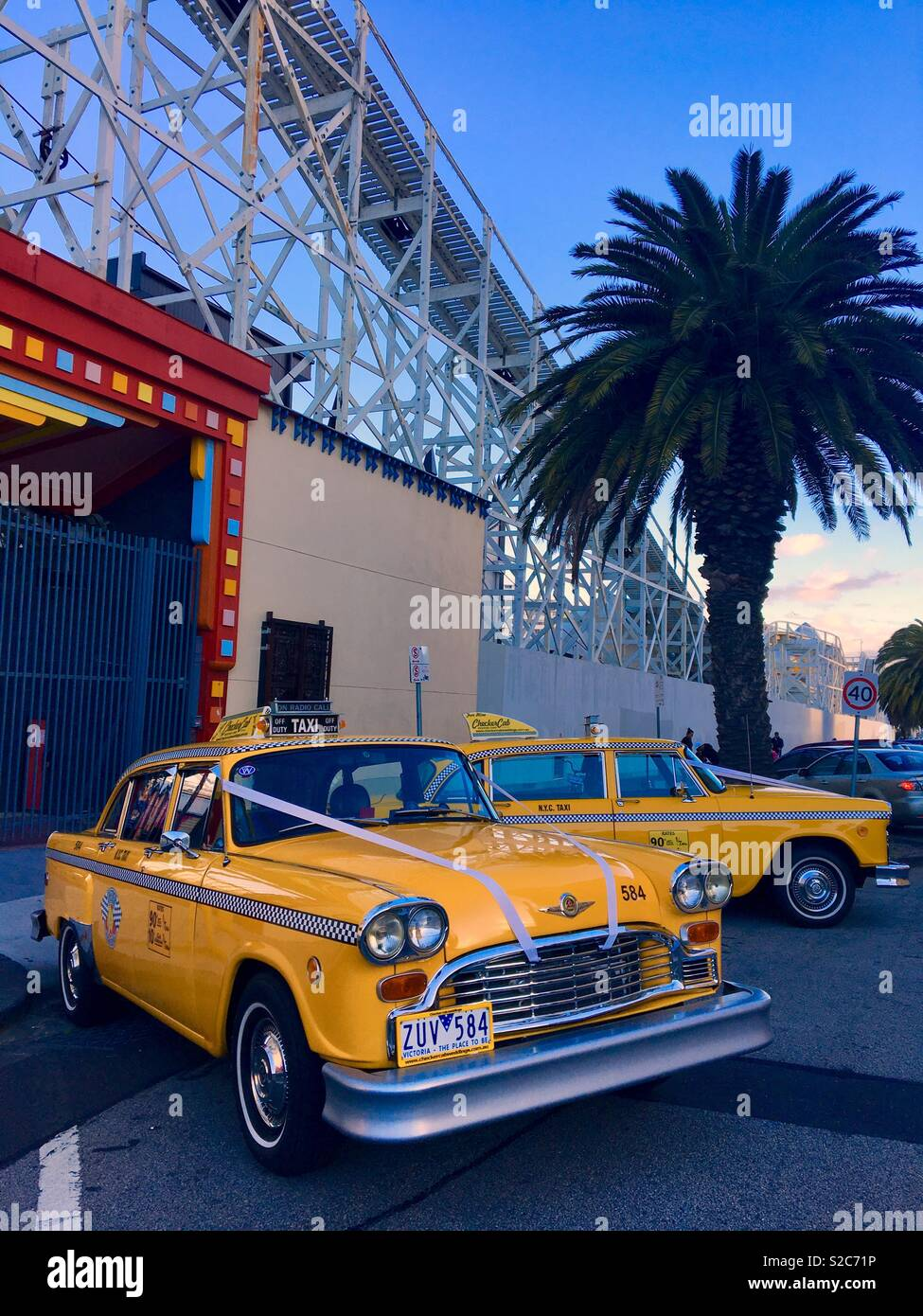 Old American Checker yellow taxi cabs for weddings at Luna Park St. Kilda in Melbourne Australia Stock Photo