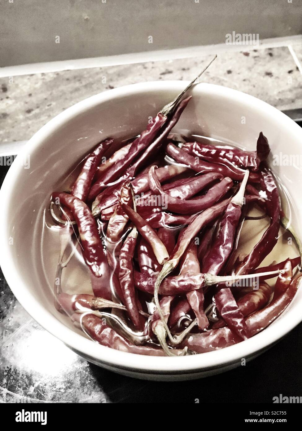 Soaking bowl of red chillies - Stock Image