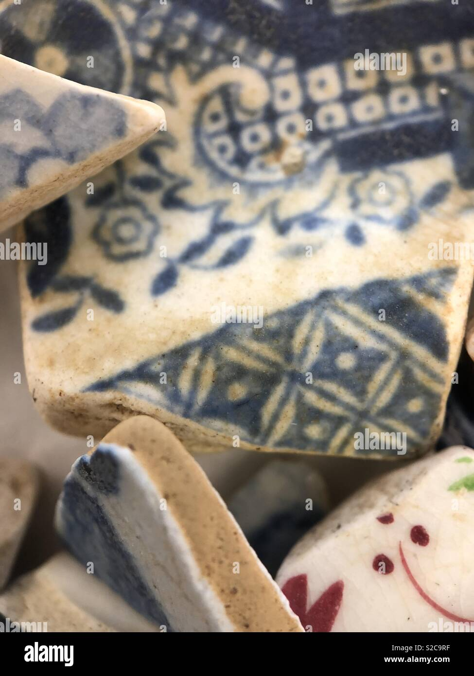 Delft pottery shards and blue and white willow ware found Mudlarking London River Thames - Stock Image