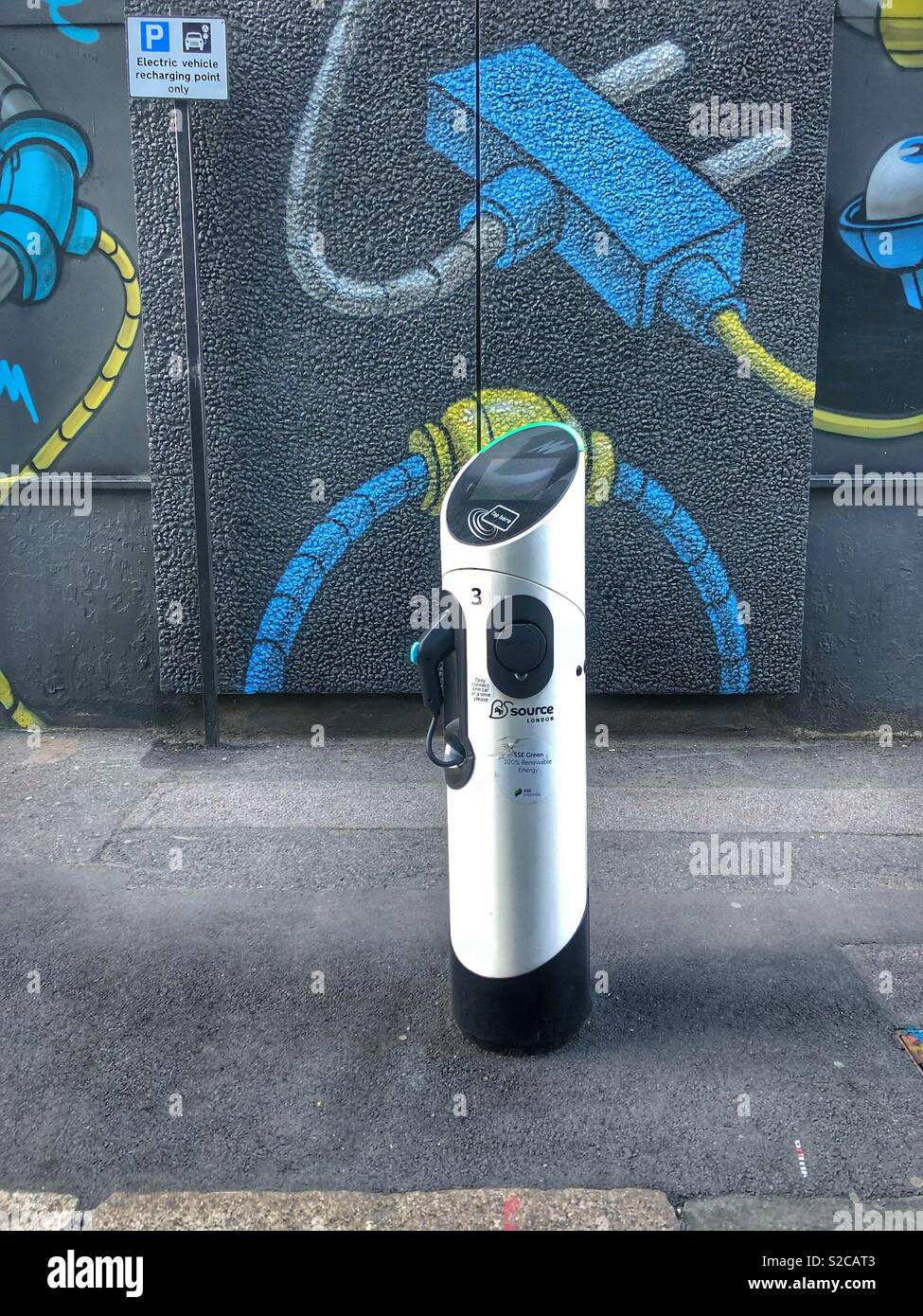 Electric car charger on pavement in shoreditch, east London, Britain. In front of street art mural. No people. Stock Photo
