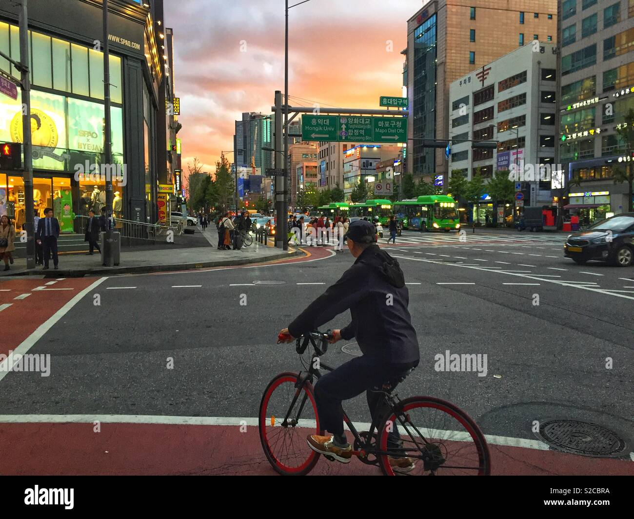 A man cycles through the busy streets of Seoul, South Korea at sunset. - Stock Image
