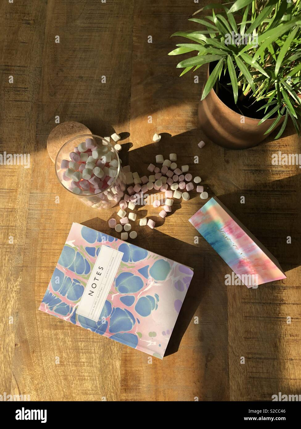 Desk flat lay with mini marshmallow sweet treats, marble patterned notebook and greeting card. Pot plant in corner - Stock Image