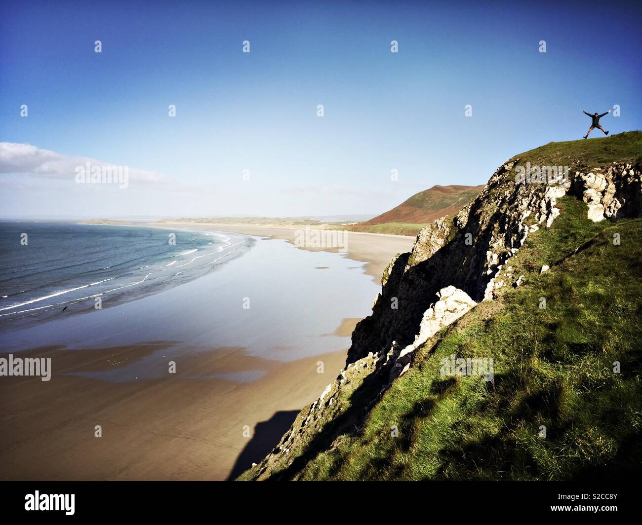 A man does a star jump on the cliff top overlooking Rhossili Bay in the Gower Peninsular in Wales. - Stock Image