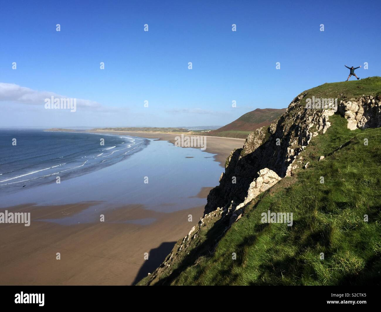 A man does a star jump on the cliff top at Rhossili Bay on the Gower Peninsular in Wales. - Stock Image