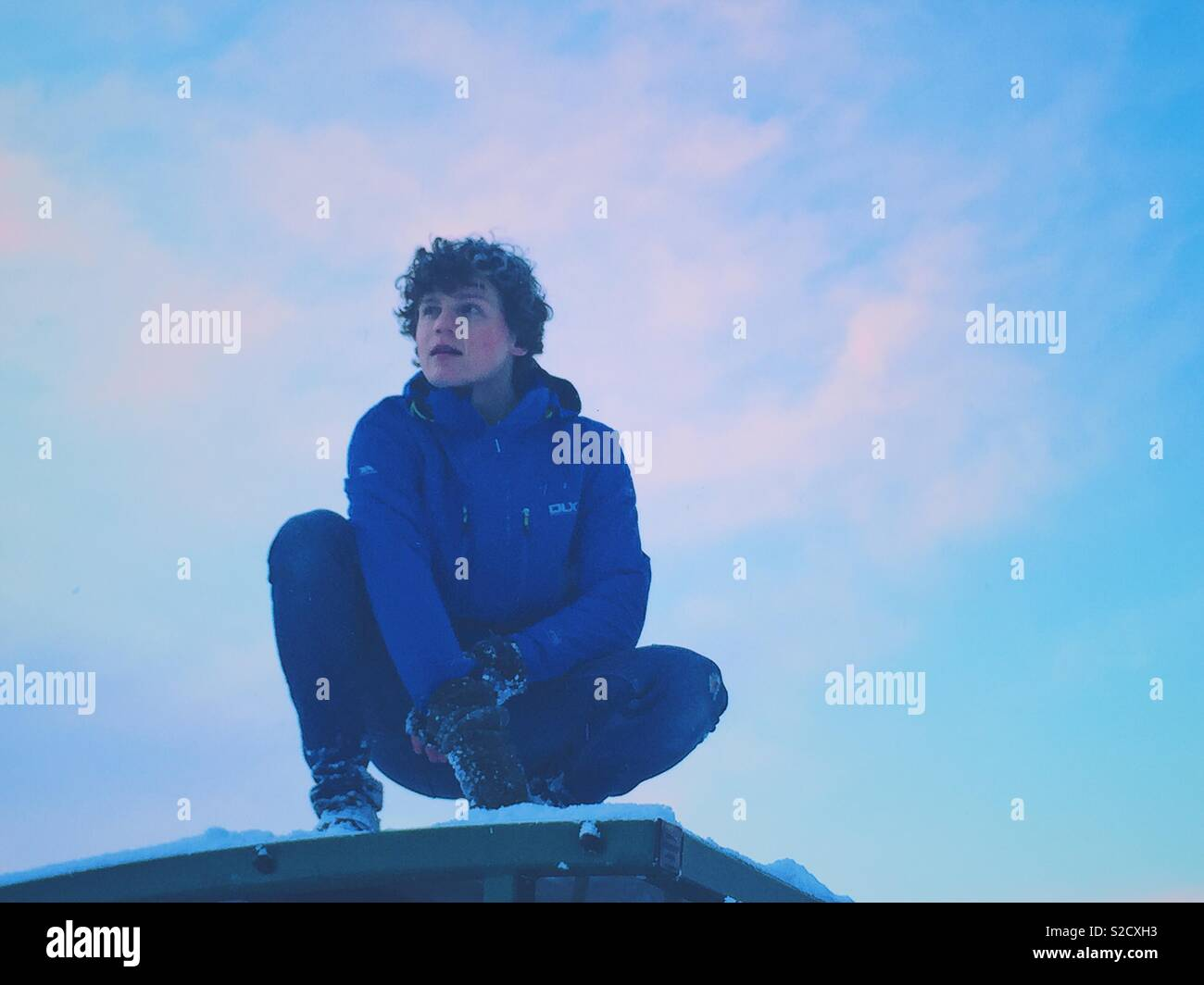 Boy crouched down on snowy rooftop, blue sky in the background - Stock Image