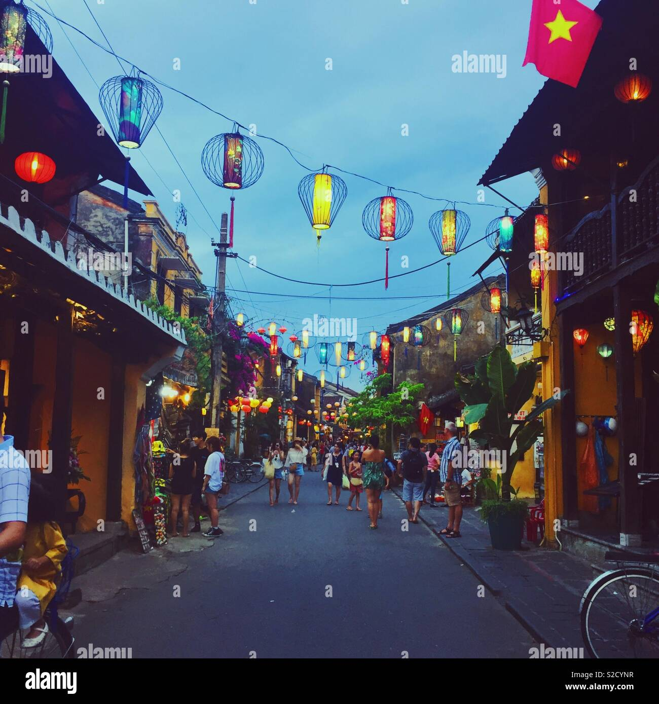 Colourful lanterns in a busy street in the ancient town in Hoi An, Vietnam - Stock Image