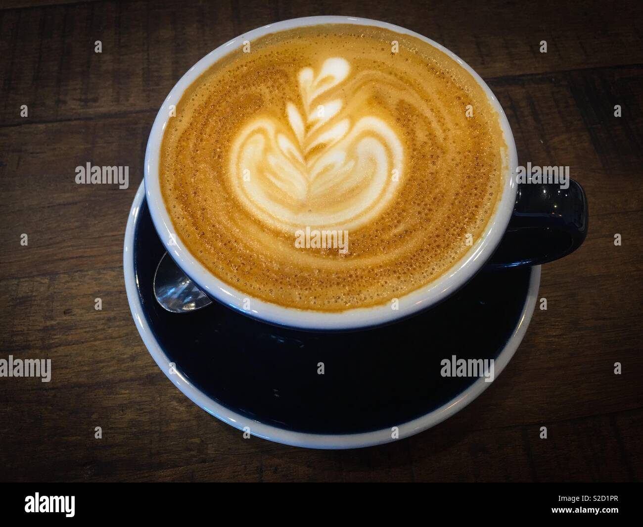 A cup of coffee latte. With a nice coffee art . For the best flavour and taste use freshly brewed coffee and full cream milk - Stock Image
