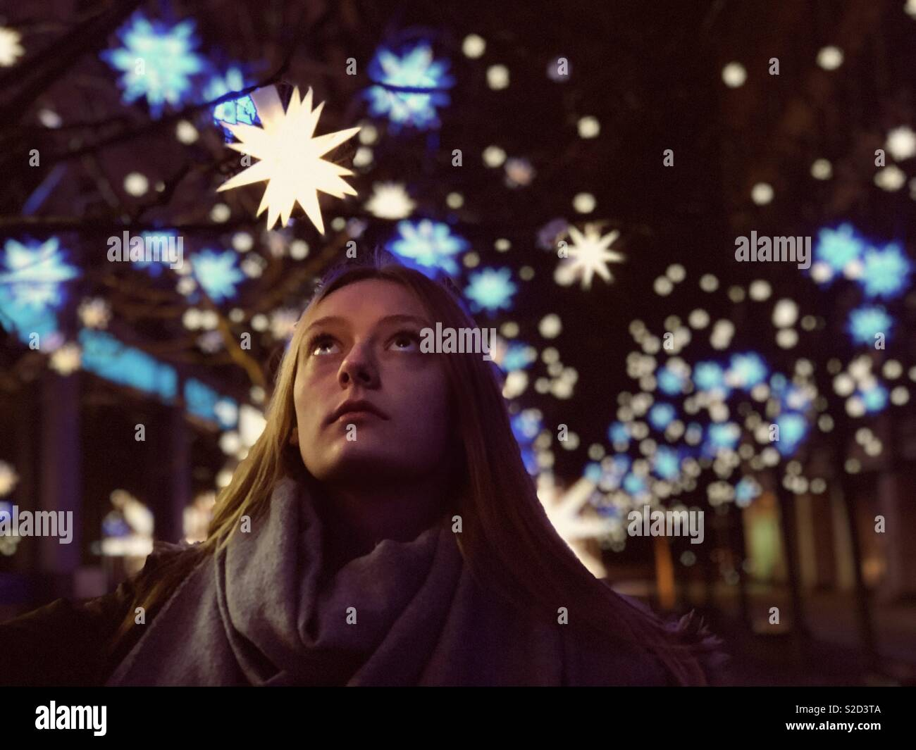 Beautiful young woman looking up to a shiny christmas star decoration. - Stock Image