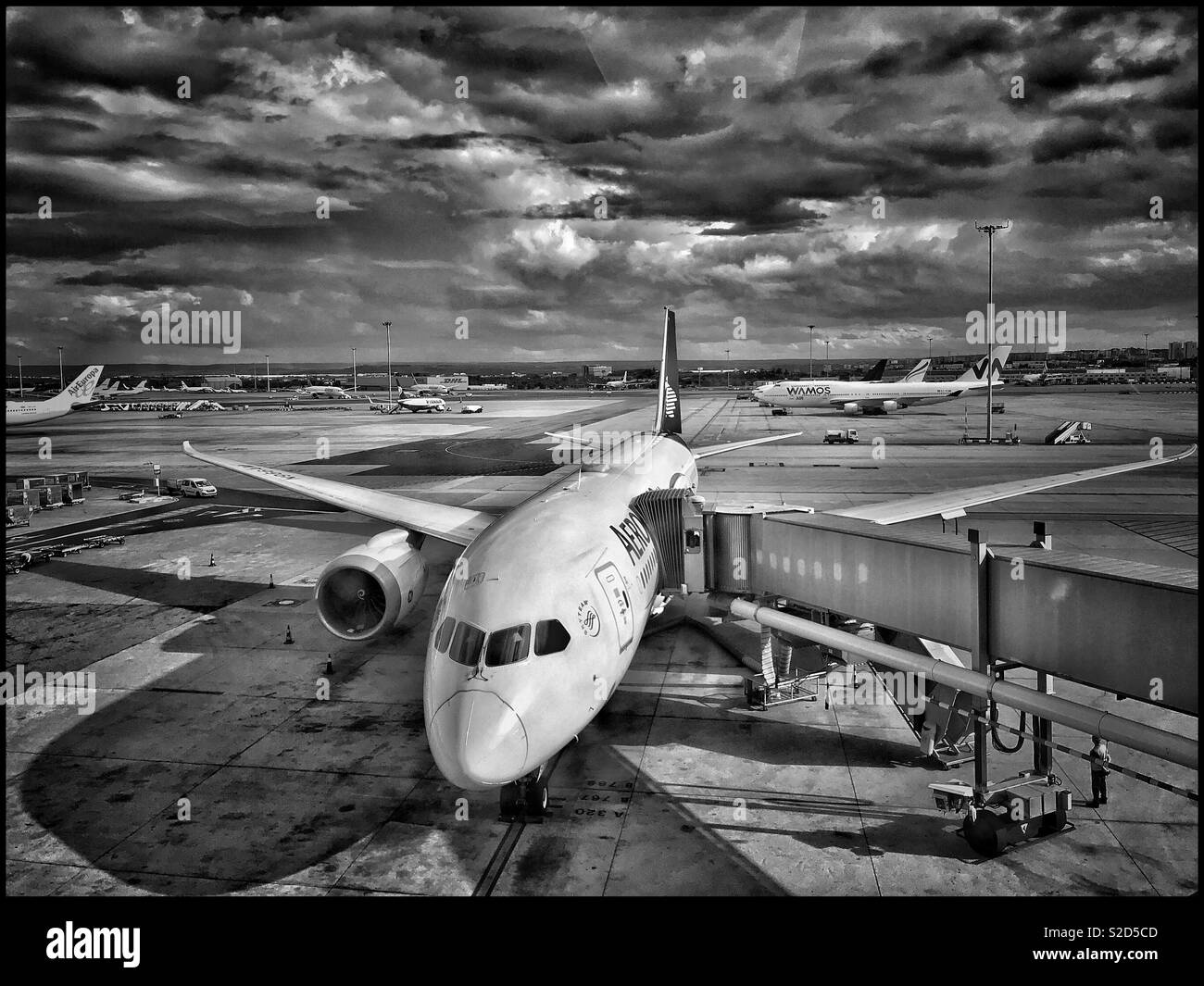 An atmospheric aerial view of aircraft at a large European airport. Despite the sunshine, it looks like rain is on the way! Photo Credit © COLIN HOSKINS. Stock Photo
