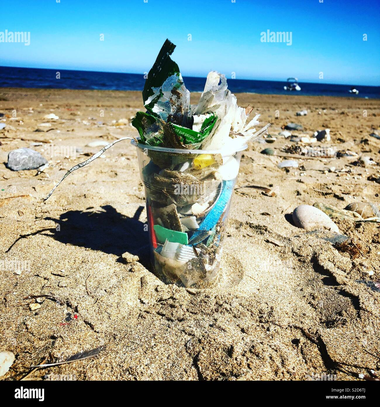 Plastic half pint cup filled with small plastics collected along a beach in Crete, Greece - Stock Image