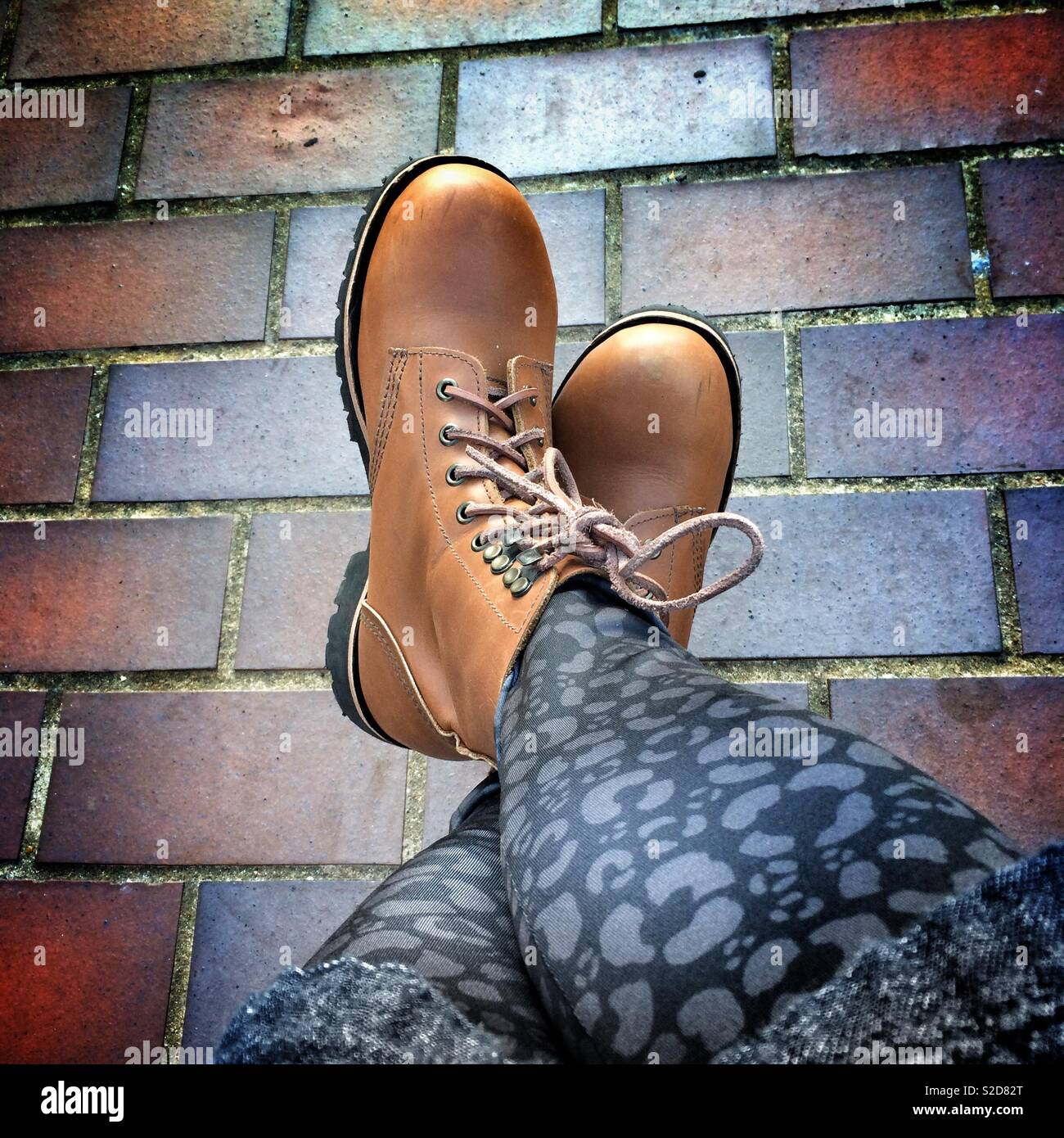 A woman's legs wearing black leopard print leggings and tan coloured lace up work boots - Stock Image