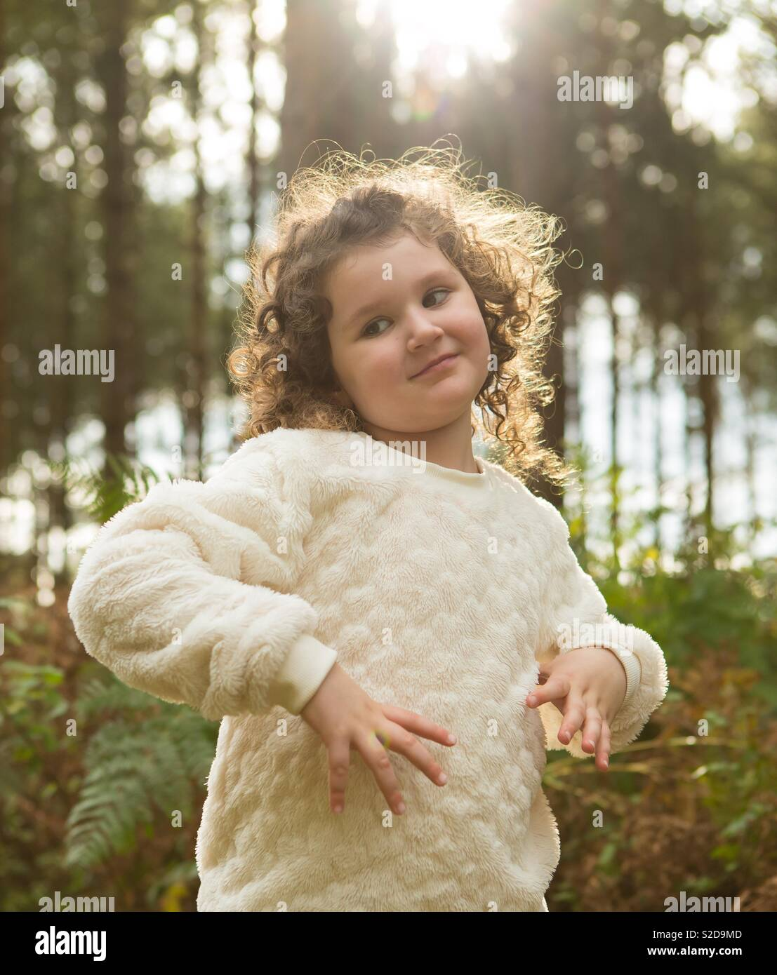 Beautiful curly haired young girl stood in the sunshine in the woodland forest at Cannock Chase, Staffordshire. - Stock Image