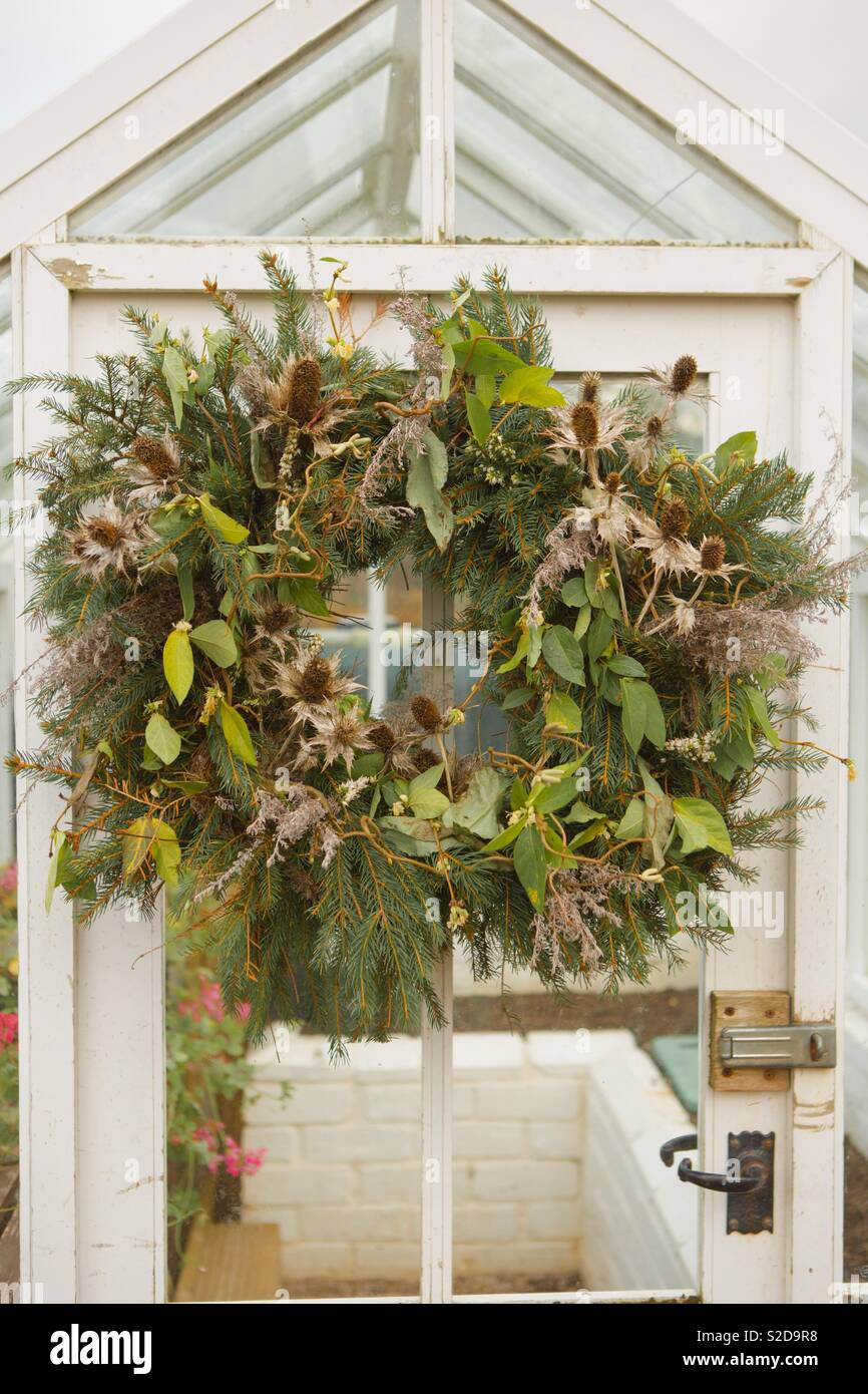 Beautiful festive winter wreath on distressed white greenhouse door. Natural wreath with winter foliage, neutral colours, Christmas wreath. - Stock Image
