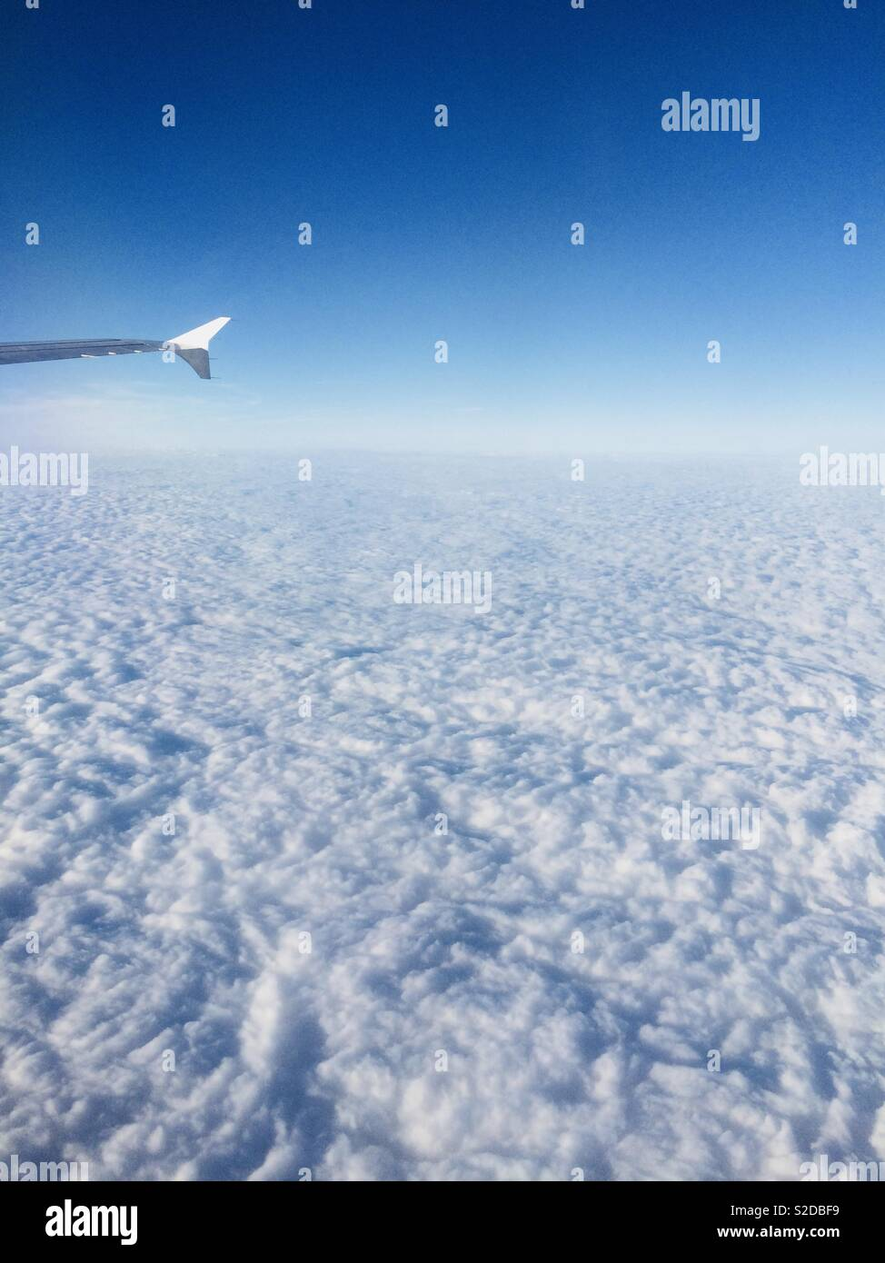View from an aeroplane window (somewhere above Europe) looking down at the clouds - Stock Image