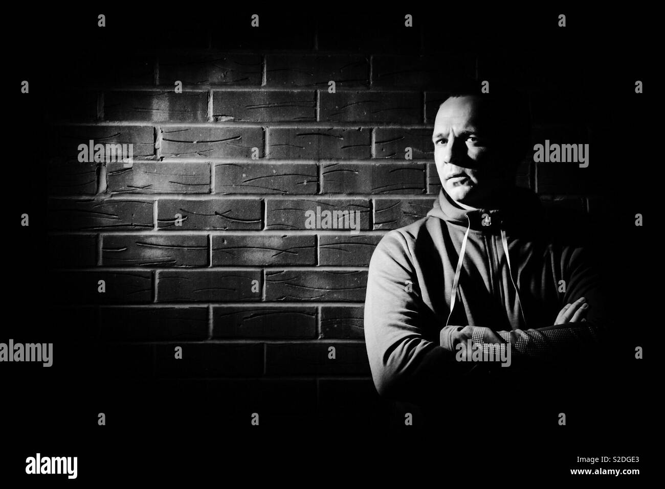 Portrait in the dark against brick wall - Stock Image