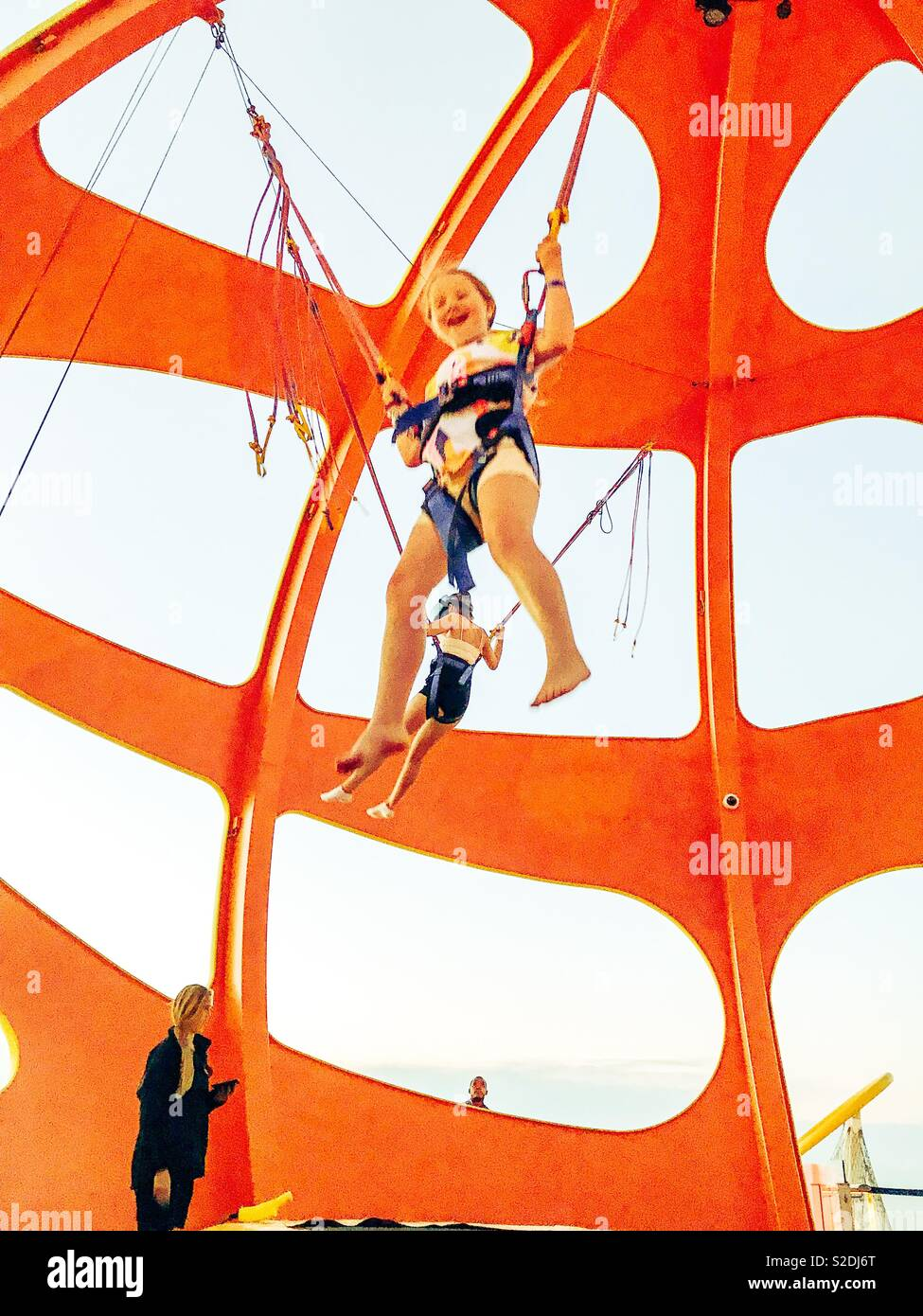 Young girl wearing harness while jumping on trampoline on the Independence of the Seas cruise ship - Stock Image