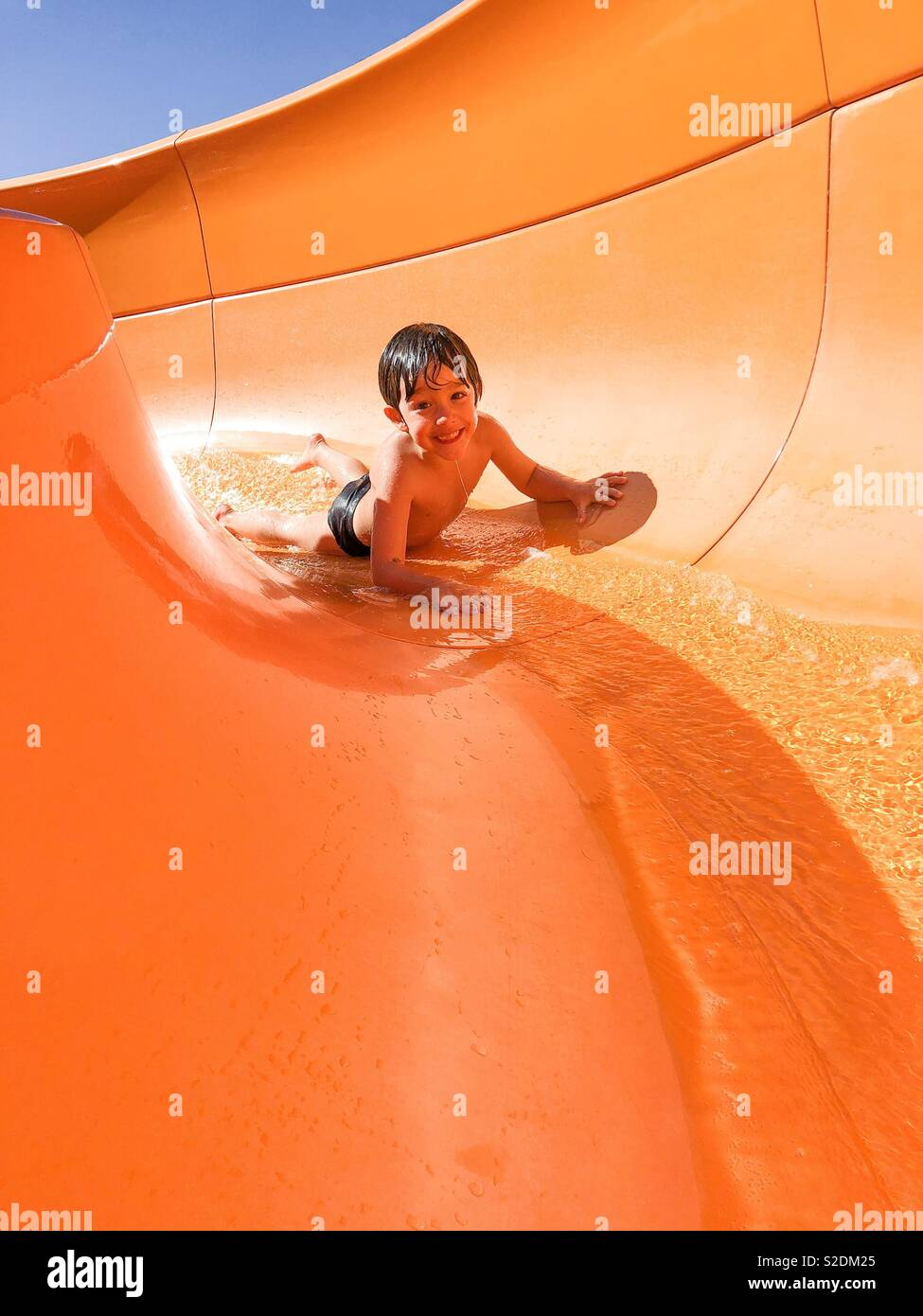 Boy going down on water slider - Stock Image