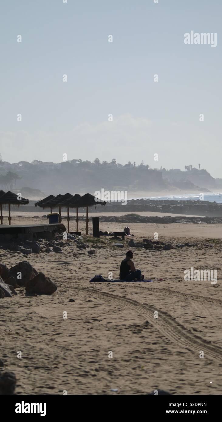 Lone Sun-worshiper, Umbrellas,Morning Beach haze - Stock Image
