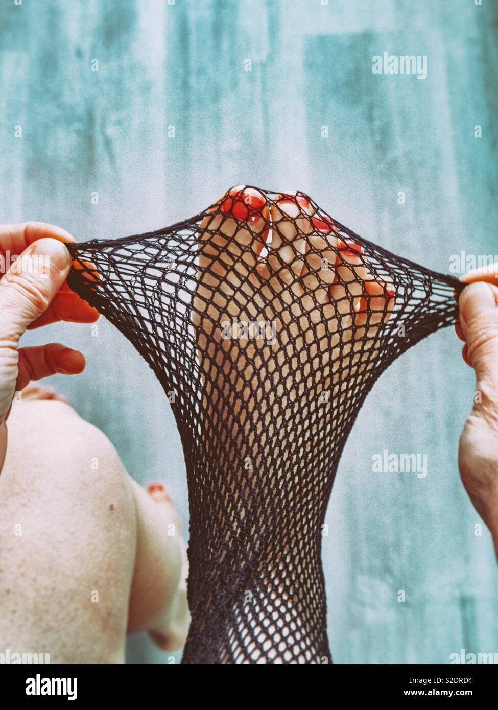 Woman putting on fishnets tights - Stock Image