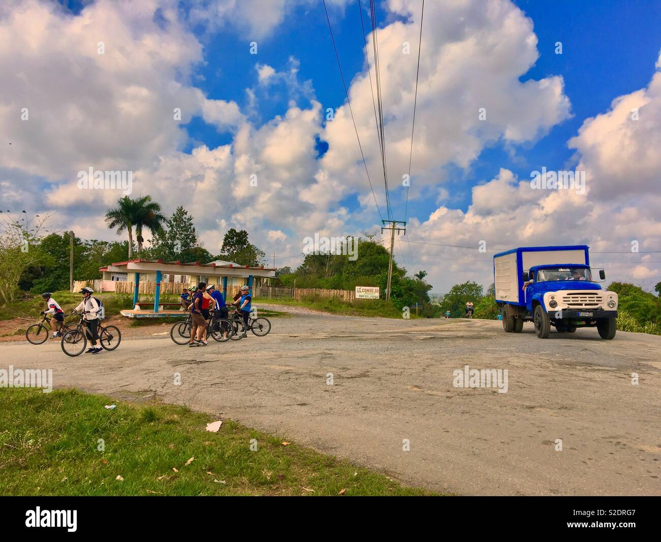 Tourists on a bicycle tour in Viñales Cuba with local Cubans passing in a old vintage truck Stock Photo