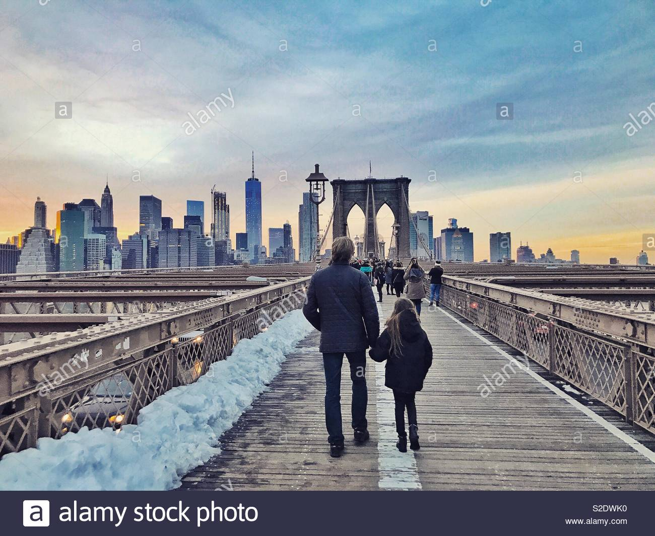 Father and daughter walking across the Brooklyn bridge toward the horizon of the Manhattan skyline in the setting sun during winter - Stock Image