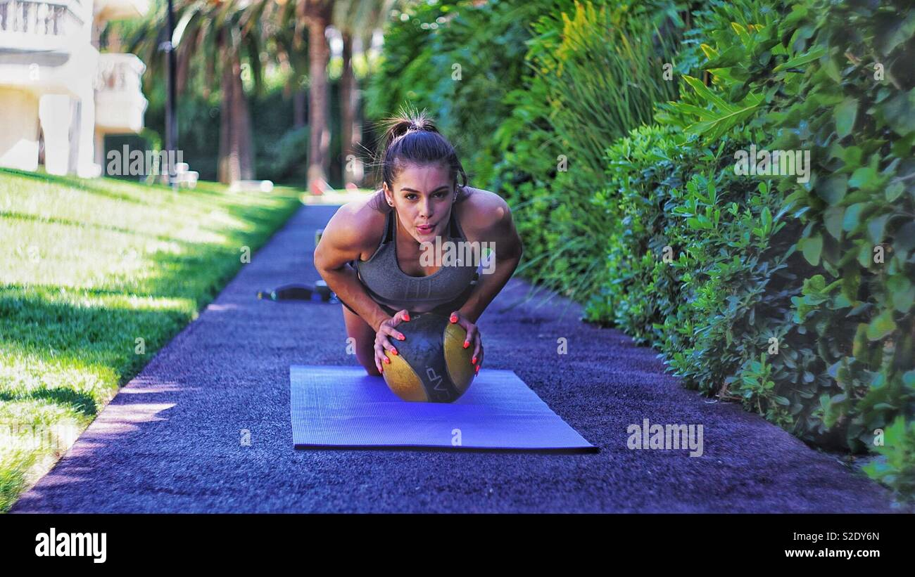 Working out.  Push ups with a medicine ball. - Stock Image