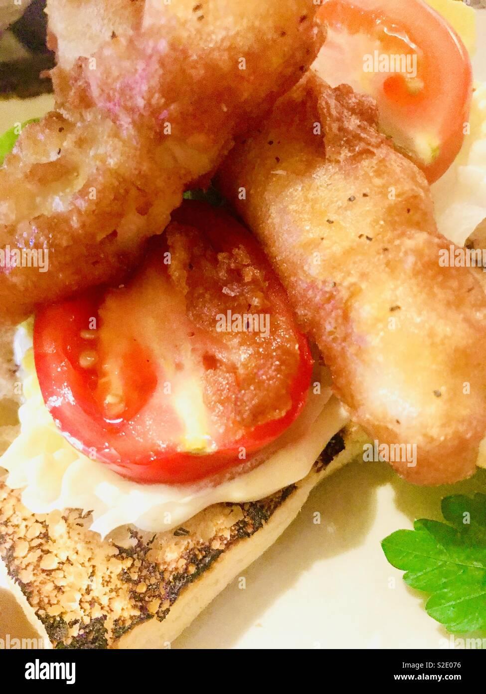 Posh fish finger sandwich with tomato - Stock Image