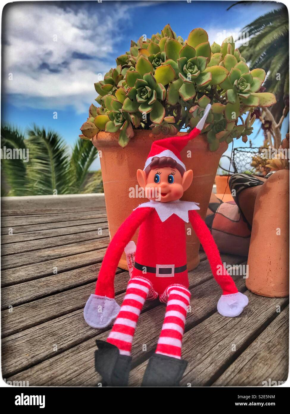 Naughty elf sitting on a table. Stock Photo