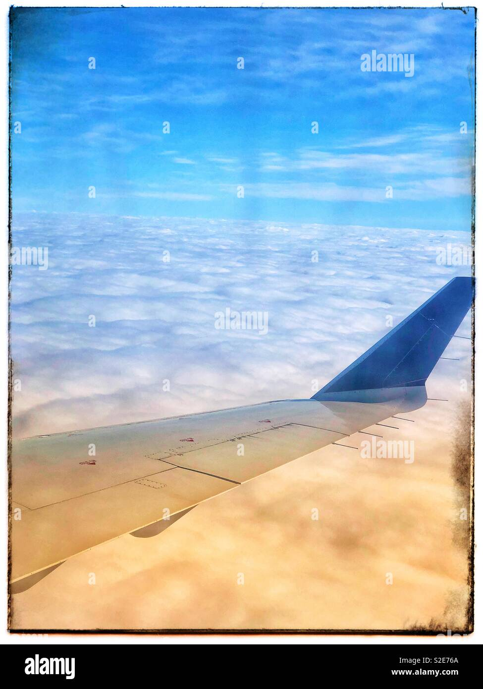 Airplane wing in the clouds - Stock Image