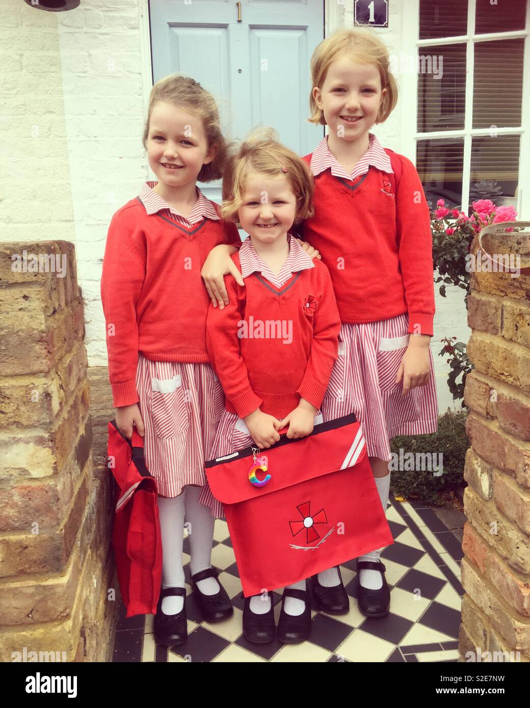 3 young sisters / kids / children / Sister / young kid / girls / girl standing at the front door ready to go to school on the first day of a new term. They are all primary school children. Uk - Stock Image