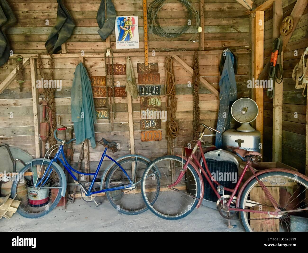 Old garage with old bicycles and number plates - Stock Image