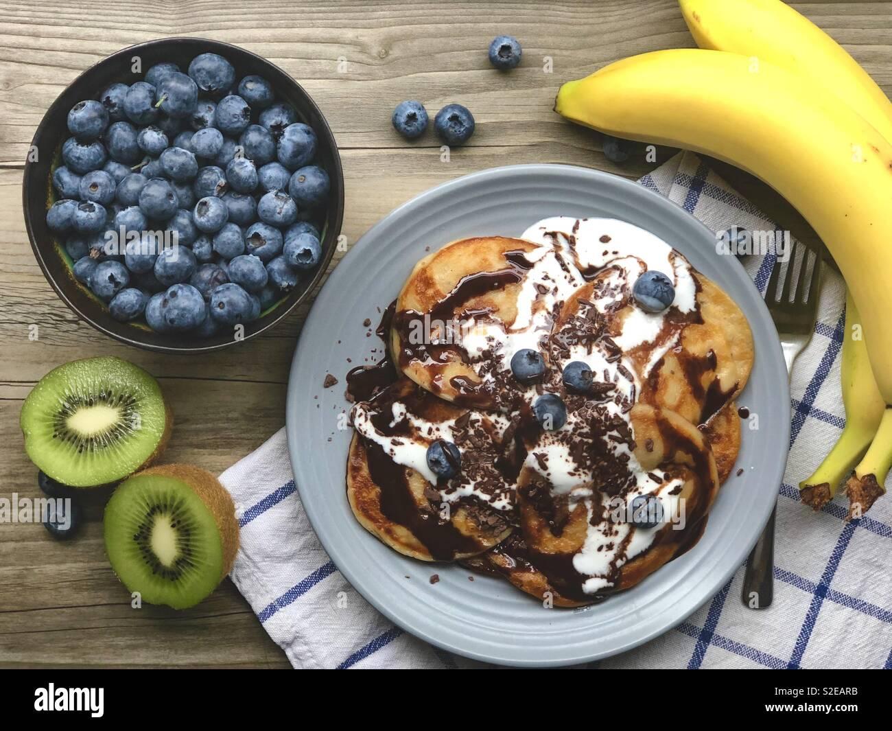 Vegan banana pancakes with blueberries , kiwi and banana slices Stock Photo