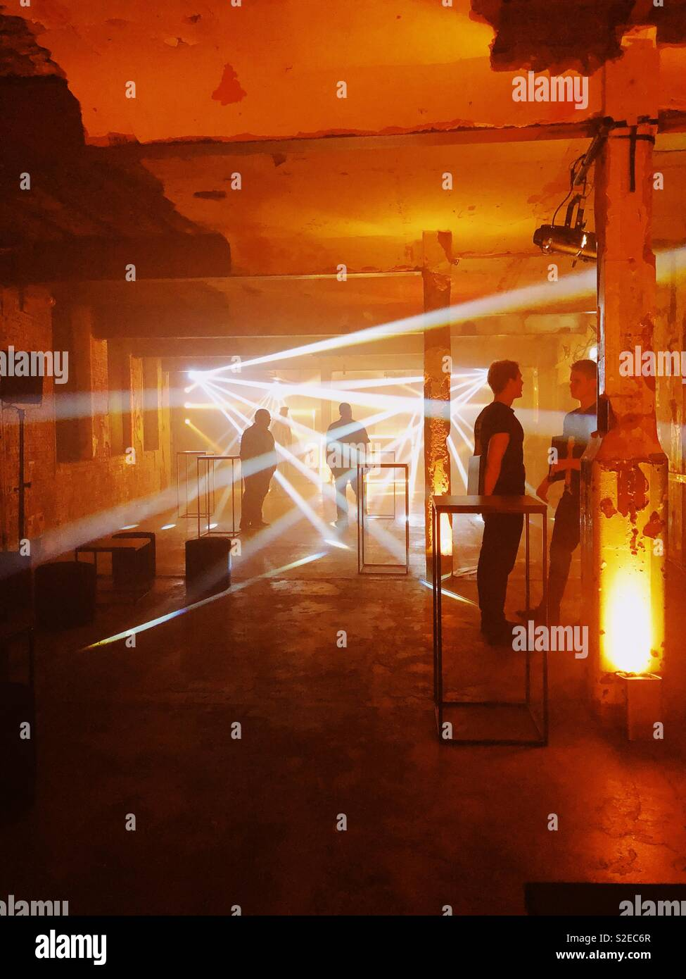 Setting up a warehouse party or rave in an industrial style old building with golden and orange toned lighting effects and organisers talking - Stock Image