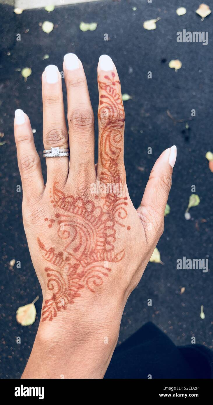 An Indian female hand with mehndi or henna on her hand Stock Photo
